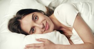 Woman Waking Up. Close up of beautiful fresh woman waking up in white bed, sunny holiday morning concept stock footage