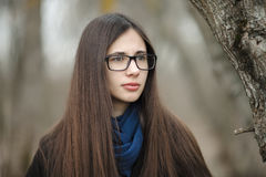 Close up beautiful girl in a black coat blue scarf glasses walking in the autumn / spring forest park. An elegant brunette girl wi Royalty Free Stock Photography