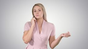 Beautiful girl blonde, speaking with someone on phone on gradient background. stock footage