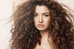 Close up of beautiful girl with curly hair looking at camera over pink background. Stock Photos
