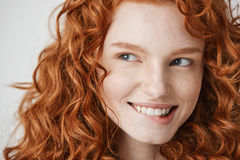 Close up of beautiful girl with curly red hair and freckles smiling biting lip over white background. Royalty Free Stock Photos