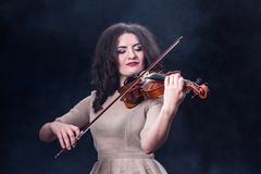 Close-up. Beautiful girl with dark hair on a smoky background. Violin and bow in female musical hands. Beautiful girl Royalty Free Stock Images