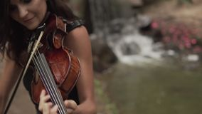 Close up of Beautiful girl in dress playing violin in forest with waterfall. Young violinist plays with inspiration. Beautiful girl in black dress playing violin stock video footage