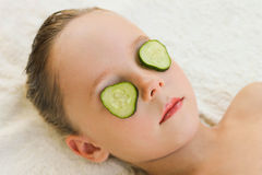 Close up of beautiful girl with facial mask of cucumber Stock Image