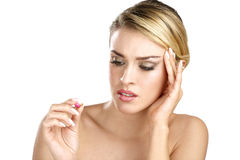 Close up of a beautiful girl having a pill for headache Royalty Free Stock Images