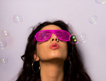Close up of a beautiful girl with professional make-up blowing soap bubbles around her. A close up shot a beautiful young girl with red lipstick and a royalty free stock photos