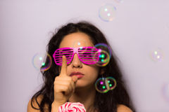 Close up of a beautiful girl with professional make-up blowing soap bubbles around her Royalty Free Stock Photography