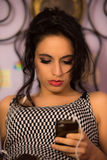 Close up of a beautiful girl with professional make-up looking at her phone. A close up shot a beautiful young girl with red lipstick and a professional make up royalty free stock photography