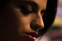 Close up of a beautiful girl with professional make-up. A close up shot a beautiful young girl with red lipstick and a professional make up in incandescent royalty free stock photo