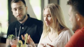 Close up of beautiful girl sitting at the bar counter with two male friends. Young woman telling a story to colleagues. Close up of beautiful girl sitting at the stock footage