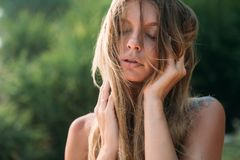Close-up of a beautiful healthy tanned face of a young girl with blond hair disheveled by the wind. The model closed her. Eyes and enjoyed thinking about royalty free stock photography
