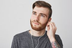 Close up of beautiful joyful charming young caucasian male student with stylish hairstyle, beard and tattoo on arm in. Casual gray t-shirt looking aside with Stock Photo