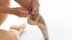 Close-up of beautiful legs of young ballerina who puts on pointe shoes on white background