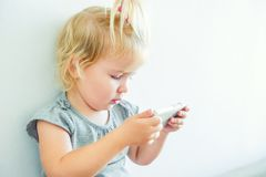 Close up Beautiful little baby girl holding and playing with smart phone on the white wall background. Children and technology con Royalty Free Stock Photo