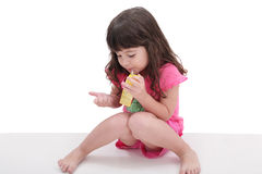 Little girl drinking from a juice box. Close-up of beautiful little girl drinking from a juice box. Shot in studio over white Royalty Free Stock Image