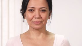 Close up of a beautiful mature Asian woman wih pink ribbon breast cancer awareness sign. Sliding close up of a beautiful mature Asian woman smiling to the camera stock footage