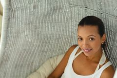 Beautiful woman at home in comfortable hanging chair. Close-up of beautiful mixed-race woman at home in comfortable hanging chair. Summer fun at home by the royalty free stock photo