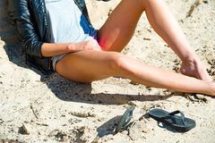 Close up of beautiful model`s legs on a beach girl wears leather. Jacket, bare feet Royalty Free Stock Image