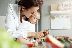 Close up of beautiful mother with dark hair cooks breakfast with her newborn baby showing him how to cut vegetables with. A knife royalty free stock photos