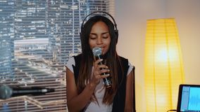 Close-up of beautiful multiracial girl in headphone singing into microphone and recording a song in home studio stock video footage
