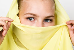 Close-up beautiful mysterious eyes eastern woman wearing a yellow hijab Royalty Free Stock Images