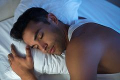 Close-up beautiful portrait of handsome man on the white bed. Close-up beautiful portrait of handsome man sleep on the white bed Royalty Free Stock Photos