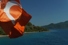 Waving flag of Turkey against the sea on a clear day. Close-up - beautiful red flag of Turkey flying in the wind on a sunny summer day royalty free stock image