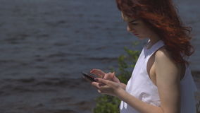 Close up of beautiful red-haired girl in a white summer dress uses a cell phone sitting on the shore and rivers stock footage