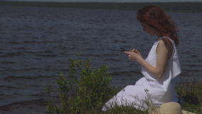Close up of beautiful red-haired girl in a white summer dress uses a cell phone sitting in social network on the shore stock footage