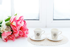Close up of beautiful red tulips in vase and two cups on a window sill. Close up of beautiful red tulips in vase and two cups on a window sill stock image