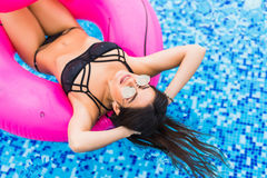 Close up of beautiful sexy girl swim on flamingo in pool in sunglasses. Summer vocation. Close up of beautiful sexy girl on flamingo in pool in sunglasses Stock Image