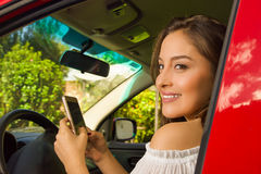 Close up of a beautiful sexy young woman in red car using her cellphone and smiling Royalty Free Stock Image