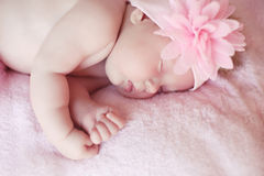 Close-up beautiful sleeping baby girl. Newborn baby girl with fl Royalty Free Stock Photography