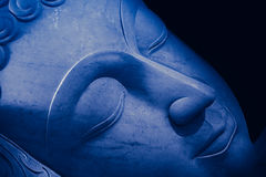 Close up beautiful sleeping Buddha face blue tone Royalty Free Stock Image