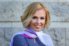 Close-up of beautiful smiling blond model near stone wall. Outdoors Stock Photos