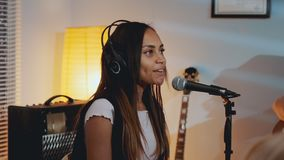 Close-up of beautiful smiling girl in headphone singing her favourite song on the rehearsal stock footage