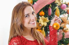 Close up of beautiful smiling woman wearing a red blouse in front of a christmas tree decorating, merry christmast and Royalty Free Stock Photo