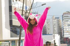 Close up of a beautiful smiling young woman wearing a pink unicorn costume, with both hands up at outdoors in the city Royalty Free Stock Photo
