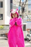 Close up of a beautiful smiling young woman wearing a pink unicorn costume, at outdoors in the city of Quito Royalty Free Stock Image