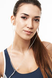 Close up of beautiful sportive girl in headphones posing looking at camera over white background. Royalty Free Stock Image