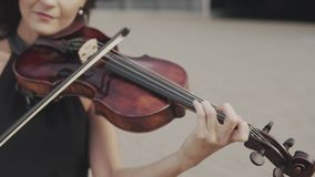 Close up of Beautiful violinist in black dress near glass building stock video