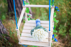 Close up of beautiful wedding bouquet on decorated swing Royalty Free Stock Images