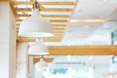 Close up of beautiful white simply modern ceiling lamps in restaurant with blurry background copy space.  Stock Photo