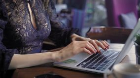Close up of beautiful woman in black sexy decolette dress sitting in cafe and using modern laptop. Businesswoman working stock footage