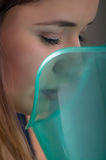 Close up of a beautiful woman doing inhalation with a vaporizer nebulizer machine on grey background Royalty Free Stock Images