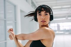 Woman warming up for workout at gym. Close up of beautiful woman doing stretching exercises at gym. Female warming up for workout at gym Royalty Free Stock Photo