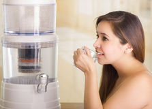 Close up of a beautiful woman drinking a glass of water with a filter system of water purifier on a kitchen background Stock Photos