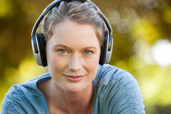 Close-up of beautiful woman enjoying music in park Royalty Free Stock Image
