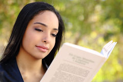 Close up of a beautiful woman reading a book in a park Royalty Free Stock Image