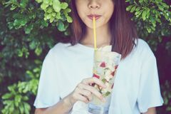 Close up of beautiful woman relaxing eat drink fruit juice in the garden. Stock Photo